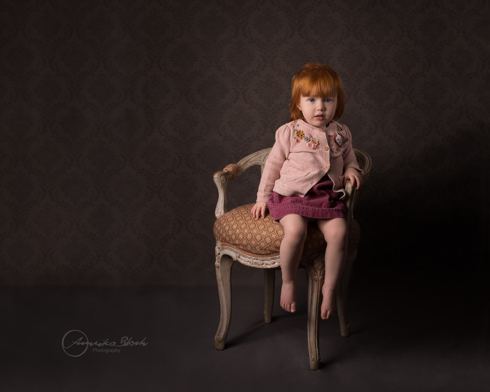 Little  red haired girl sitting on a chair